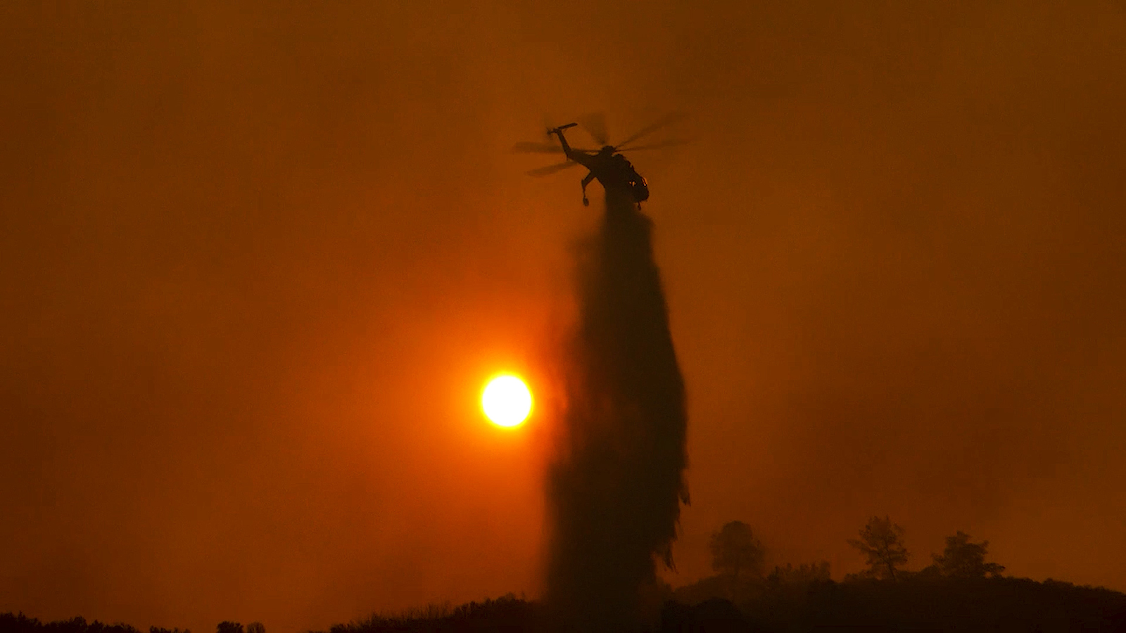 Helicopter dumping water on wildfire in sunset